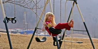 Child on a swing with fracking site in the background