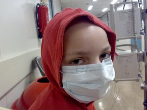 A young girl with leukemia, wearing a hoody over her bald skull and breath protector.