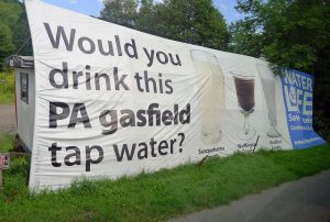 Huge banner showing three glasses w/ muddy water from different fracked counties in Pennsylvania.