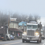 Frack trucks on town road emitting particulate matter.